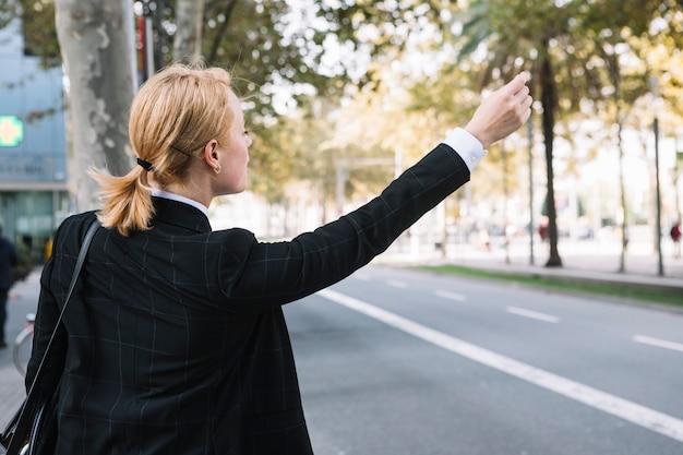 Вид сзади молодой женщины родом автомобиль такси rideshare на дороге Бесплатные Фотографии