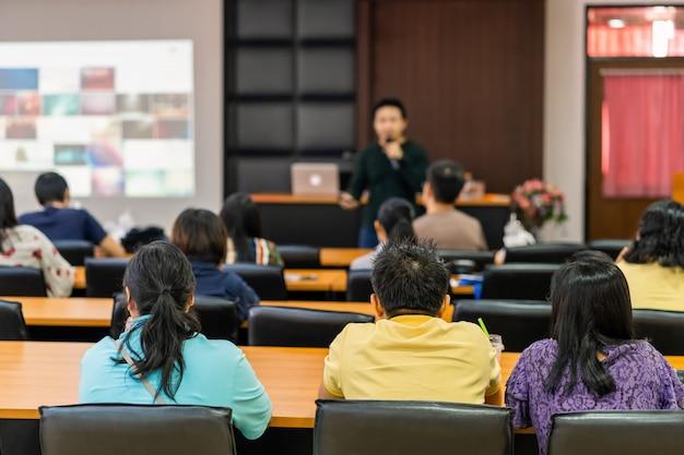 会議ホールやセミナー会議、ビジネス、投資の概念についての教育のステージで聴衆のスピーカーを聞いての背面図 Premium写真