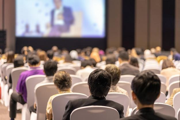 会議ホールまたはセミナー会議、投資に関するビジネスおよび教育のステージで聴衆を聞くスピーカーの背面図 Premium写真