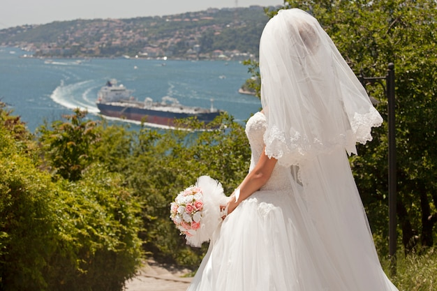 Rear view of bride with bouquet looking at bay Free Photo