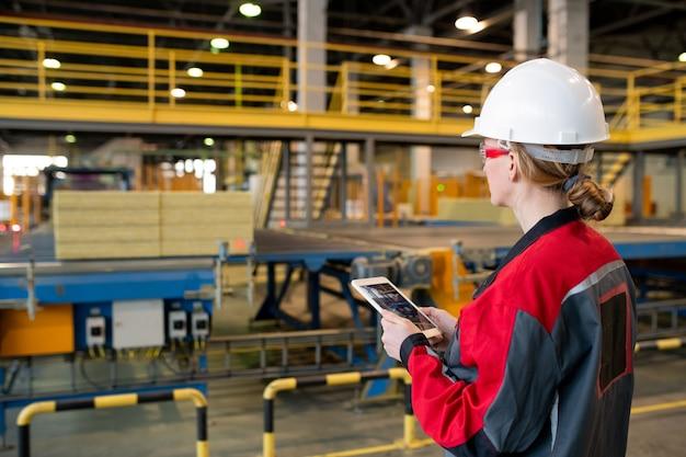 공장에서 생산 라인 공정을 제어하면서 태블릿을 사용하는 안전모 및 안전 고글의 바쁜 여성의 후면보기 프리미엄 사진