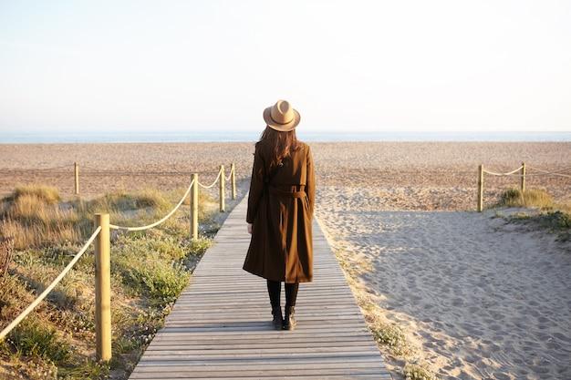 Вид сзади модной женщины с распущенными темными волосами стоял один на променаде, направляясь к морю. до неузнаваемости молодая женщина в шляпе и пальто пришла в океан, чтобы очистить голову, сталкиваясь со стрессом на работе Бесплатные Фотографии