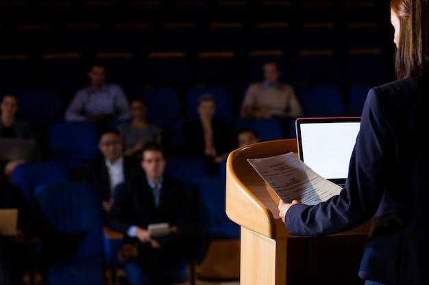Вид сзади женского руководителя бизнеса, выступая с речью Бесплатные Фотографии