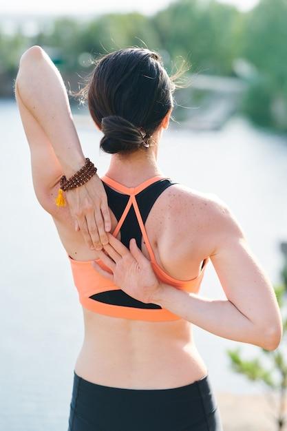 Вид сзади подтянутой женщины с пучком волос, созерцающей озеро и держащей руки вместе Premium Фотографии