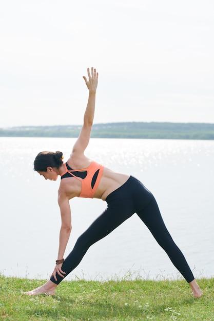 健康な体と草の上に立って、湖の岸に拡張三角形のポーズをしている精神を持つ少女の背面図 Premium写真