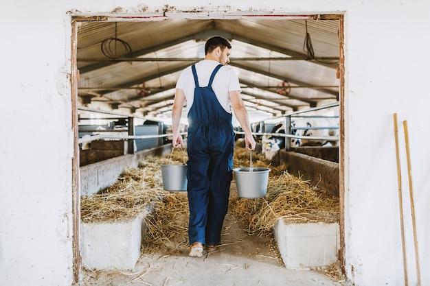 動物性食品を手に全体的なバケツを持ってハンサムな白人農家の背面図。安定したインテリア。 Premium写真