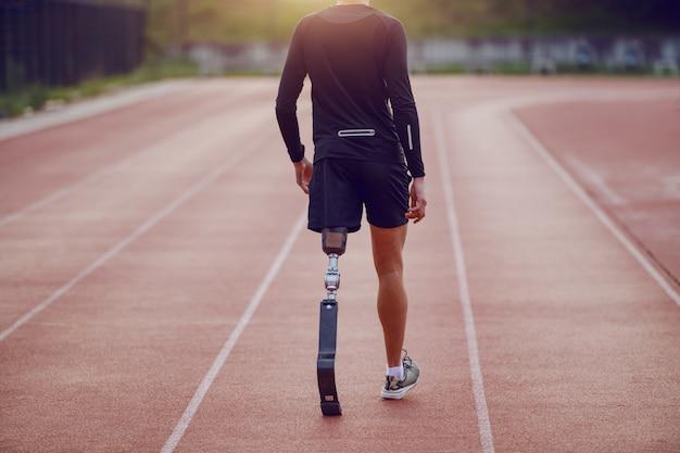 잘 생긴 백인 장애인 젊은이의 후면보기 인공 다리와 반바지와 경마장에 걷는 운동복 입고. 프리미엄 사진