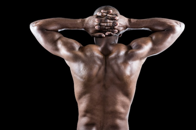 Rear view of muscular athlete stretching with hands behind head ...