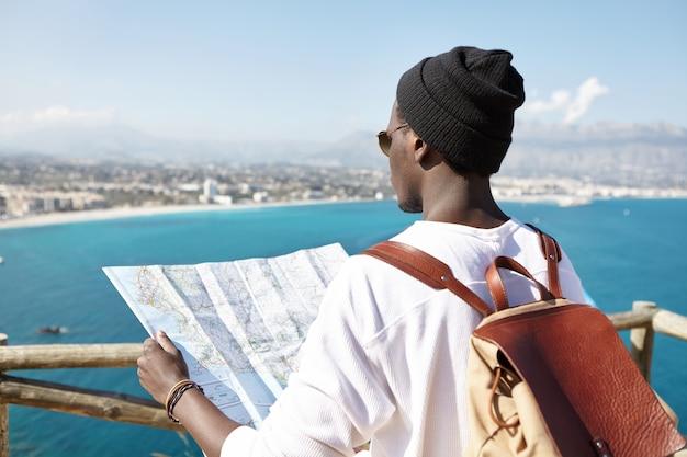 海岸に沿って彼の前の美しい場所と場所に関する情報を読んで、紙のガイドを保持している彼の肩に革のバックパックを備えたファッショナブルなアフロアメリカンハイカーの背面図 無料写真