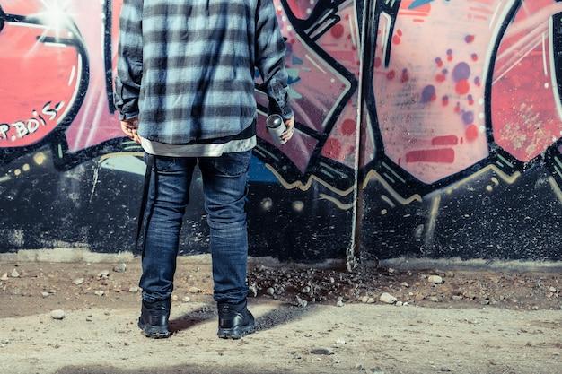 Вид сзади человека, стоящего перед граффити, держащего бутылку с распылителем Бесплатные Фотографии