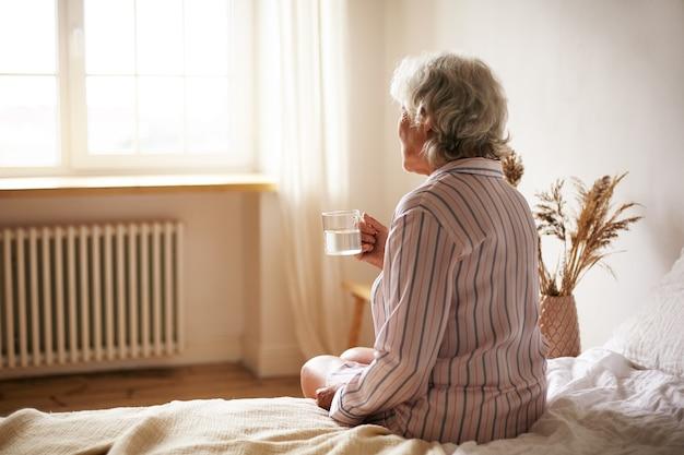 불면증으로 고통받는 수면제를 씻는 찻잔을 들고 회색 머리를 가진 수석 60 세 여성의 후면보기. 침실에 앉아 물으로 약을 복용하는 노인 은퇴 여성 무료 사진