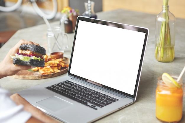 Вид сзади студента, сидящего перед открытым универсальным ноутбуком с гамбургером в руке Бесплатные Фотографии
