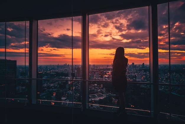 Вид сзади женщины смотря горизонт токио и взгляд небоскребов на смотровой площадке на заходе солнца в японии. винтажный тон Premium Фотографии