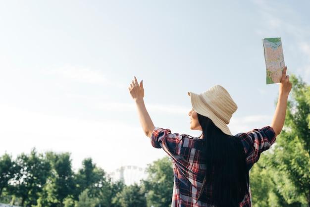 Вид сзади женщина подняла руку с держащей карту глядя Бесплатные Фотографии