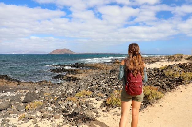 スペインのフェルテベントゥラ島の海に見える若い女性バックパッカーハイキングの背面図 Premium写真