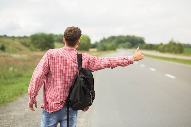 Rear view of young man with his backpack hitchhiking on straight road 23 2147874718
