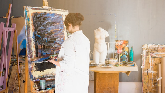 Rear view of professional artist painting at workshop Free Photo