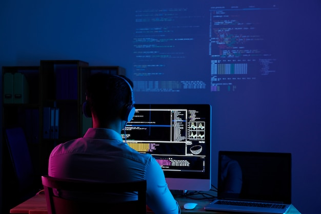 Rear view of programmer working all night long Free Photo