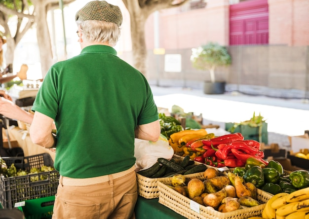 Rear view of senior man standing at vegetable and fruit stall Free Photo
