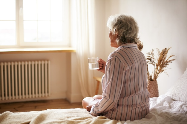 Rear view of senior sixty year old woman with gray hair holding mug washing down sleeping pill, suffering from insomnia. elderly retired female taking medicine with water, sitting in bedroom Free Photo