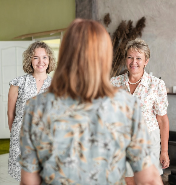 Rear view of senior woman looking at her smiling daughter and grand daughter Free Photo