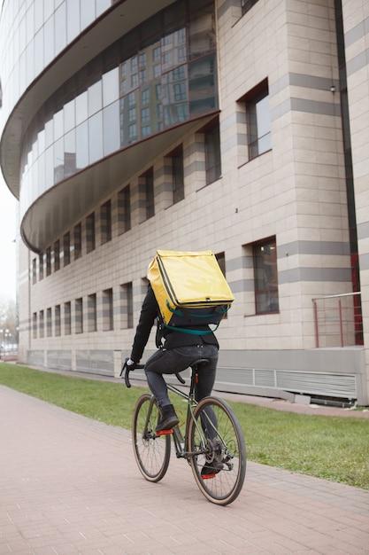 도시에서 사이클링, 열 배낭을 착용하는 택배의 후면보기 샷 프리미엄 사진