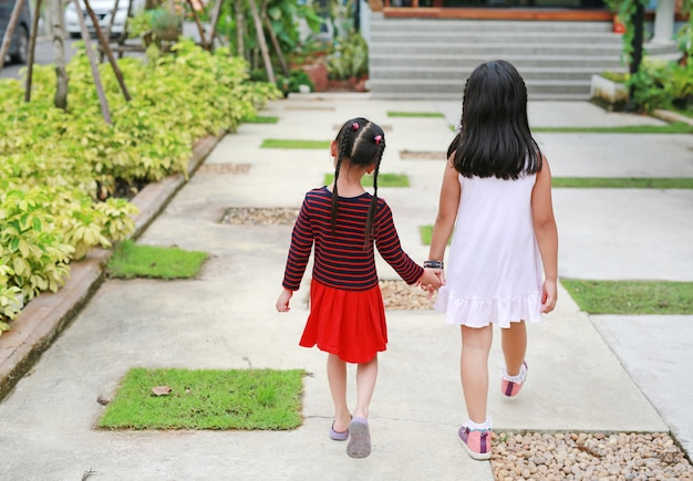 Rear view of sister hold hands with small children walking on the road garden. Premium Photo