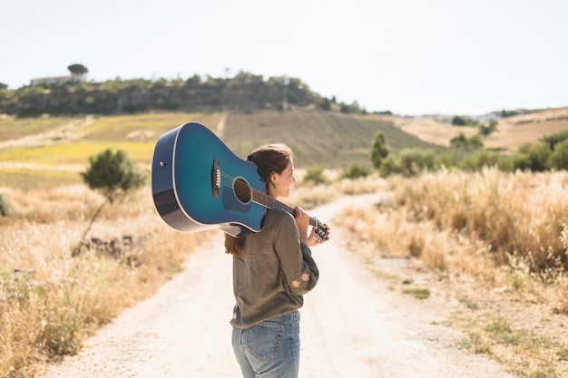 Rear view of a teenage girl standing on dirt road holding guitar Free Photo