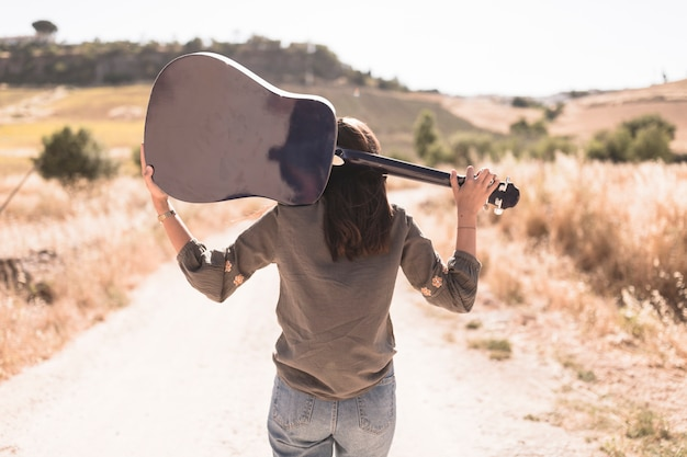 Rear view of a teenage girl with guitar standing on dirt road Free Photo