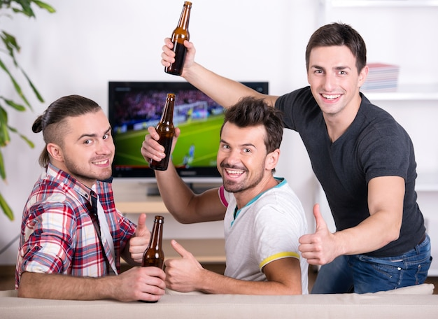 Rear view of three excited soccer fans sitting on sofa. Premium Photo
