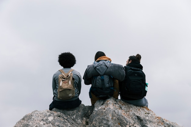 Rear view of a three friends sitting on rock against sky Free Photo
