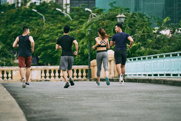 Rear view of three man and a girl jogging together on a summer day Free Photo