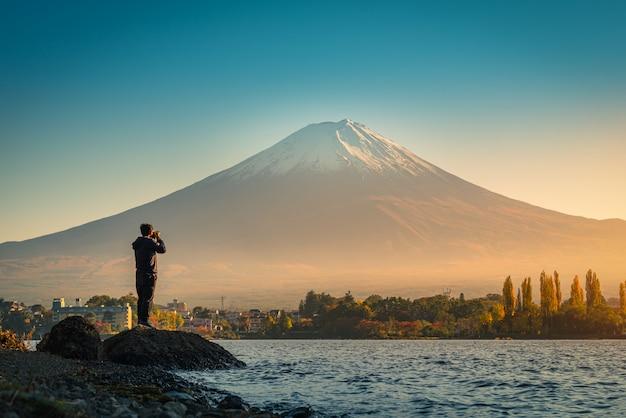 Rear view of traveler man take photo fuji mountain and kawaguchiko lake at sunset in kawaguchiko, japan. Premium Photo