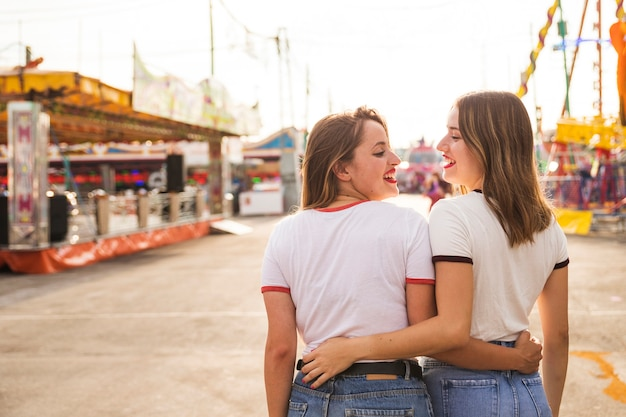 Rear view of two happy women walking at amusement park Free Photo