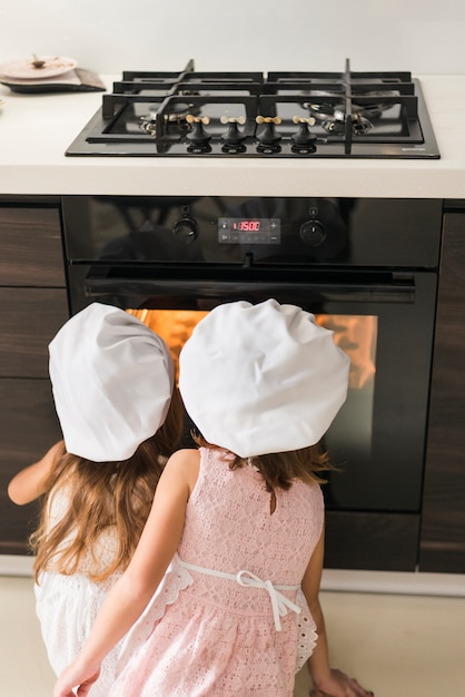 Rear view of two kids in chef hat looking at cookie tray in oven Free Photo