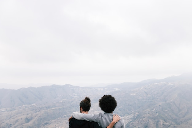 Rear view of two male hikers overlooking the mountain landscape Free Photo