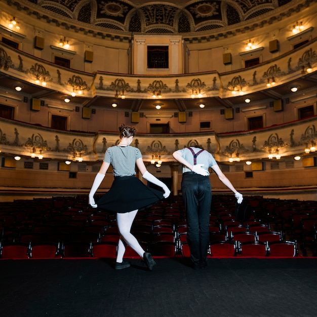 Rear view of two performer bowing on stage Free Photo