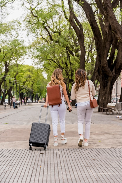 Rear view of two young women walking in the park with luggage bag Free Photo