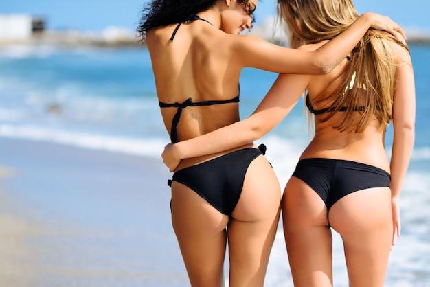 Rear view of two young women with beautiful bodies in bikini Premium Photo