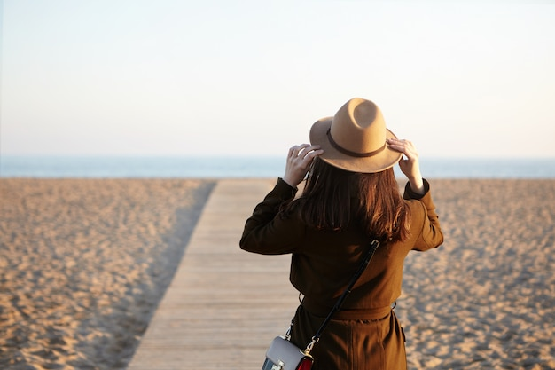 Rear view of unrecognizable brunette woman wearing hat, coat and shoulder bag standing on boardwalk along beach, enjoying nice warm day, came to the sea to make her mind after hard working day Free Photo