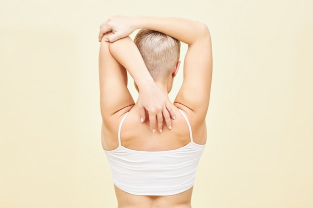 Vista posteriore di una giovane donna irriconoscibile con taglio di capelli corto da ragazzino che allunga le braccia dietro la schiena, migliorando la mobilità dell'articolazione della spalla e aprendo il torace. persone, sport e concetto di fitness Foto Gratuite