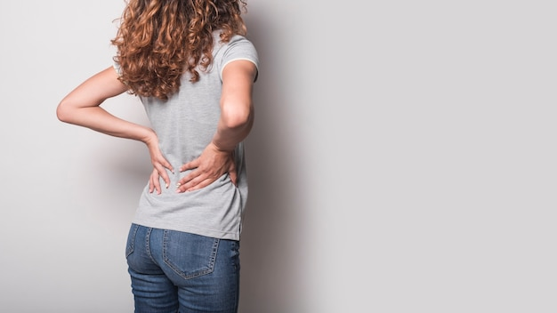 Rear view of woman having backache against gray background Free Photo