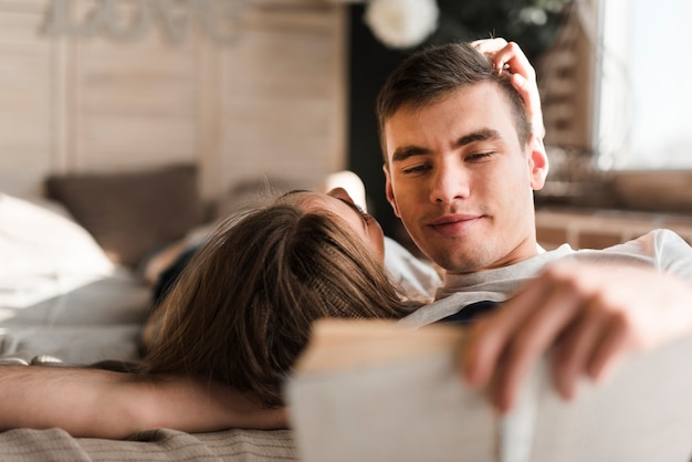 Rear view of woman lying on bed near the man reading book Free Photo