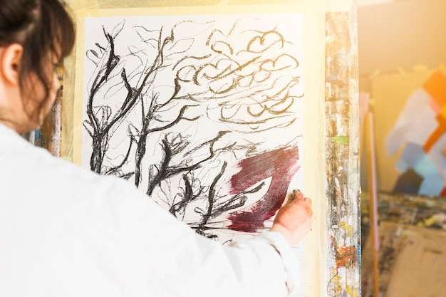 Rear view of woman painting on canvas at workshop Free Photo