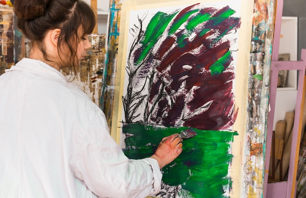 Rear view of woman painting on messy canvas at workshop Free Photo