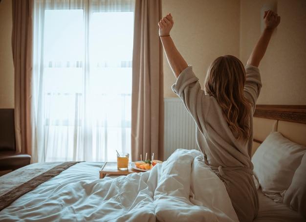Vista posteriore di una donna che si estende il corpo dopo il risveglio sul letto Foto Gratuite