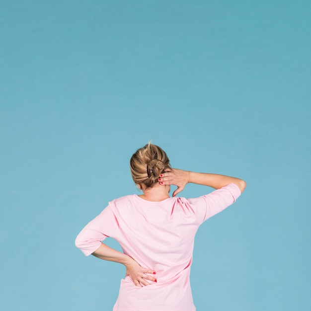 Rear view of woman suffering from backache and shoulder ache against blue wallpaper Free Photo