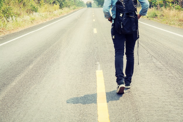 Rear view of woman walking along the road Free Photo