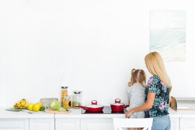 Rear view of a woman with her daughter in kitchen Free Photo