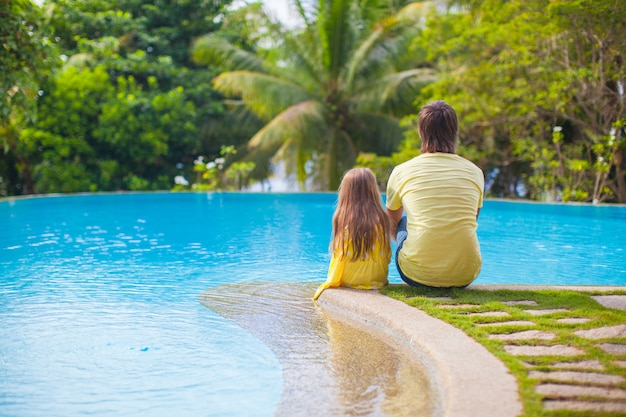 Rear view of a young father and his cute daughter sitting by the  swimming pool Premium Photo